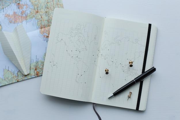 Carte de voyage, avion en papier et agenda