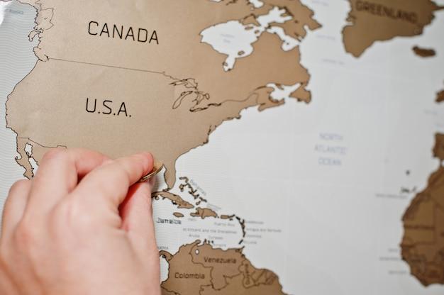 Carte de voyage du monde à gratter, main de l'homme, efface les états-unis avec une pièce de monnaie.