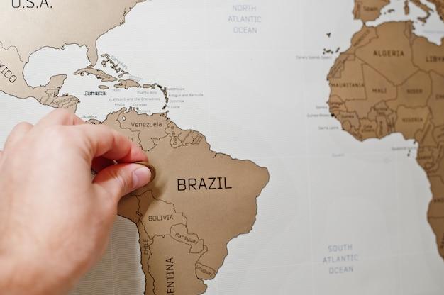 Carte de voyage à gratter du monde, main de l'homme, efface le brésil avec une pièce de monnaie.