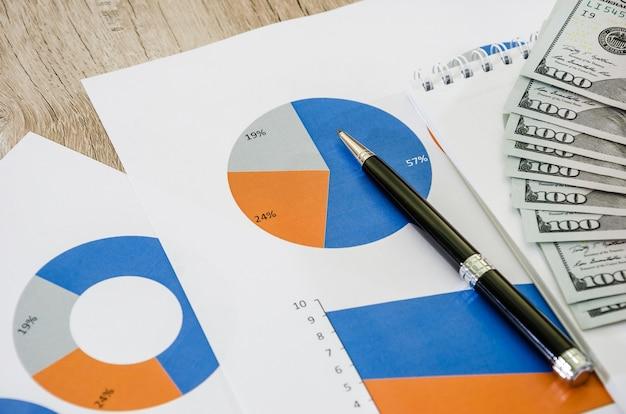 Cartes d'affaires et argent sur une table en bois dans le bureau comptabilité fiscale statistique et analytique
