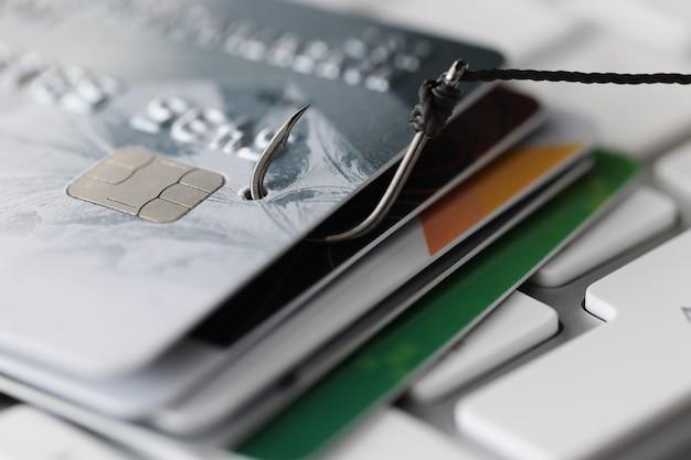 Cartes bancaires en plastique et crochet de pêche sur le concept de dépendance au crédit de clavier d'ordinateur blanc