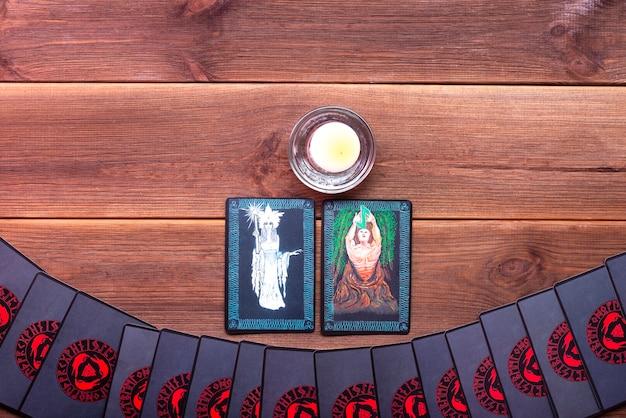 Cartes de bonne aventure sur une table en bois avec une bougie avec place pour le texte. concept de divination, cartes de tarot, médium.