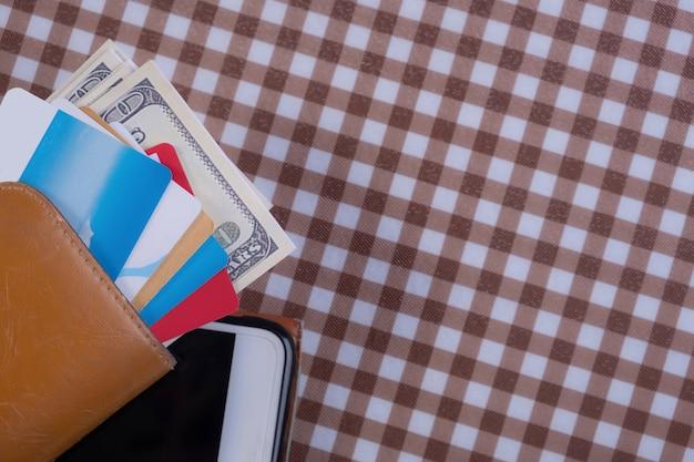 Les cartes de crédit et de l'argent dans le portefeuille mis sur un téléphone intelligent