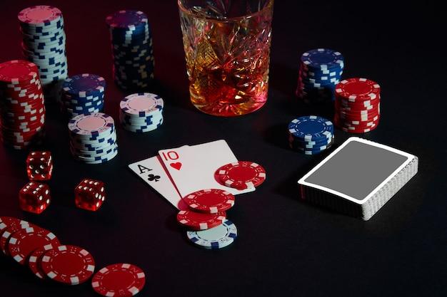 Les cartes du joueur de poker sur la table sont des jetons et un verre de cocktail avec une combinaison de cartes au whisky