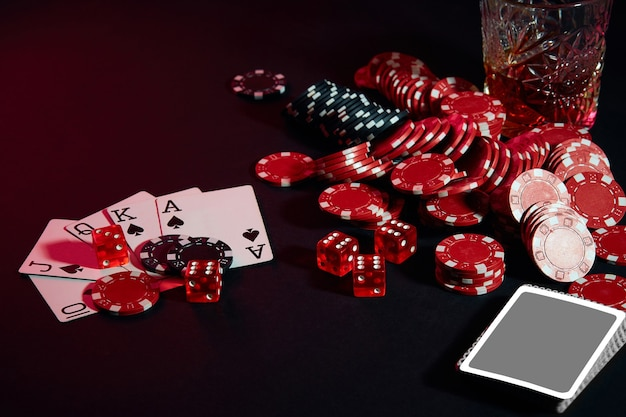 Les cartes du joueur de poker sur la table sont des jetons et un verre de cocktail avec une combinaison de whisky de voiture...