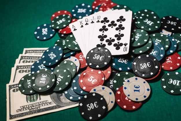 Cartes avec un flush royal sur une pile de jetons et de dollars en argent dans une partie de poker