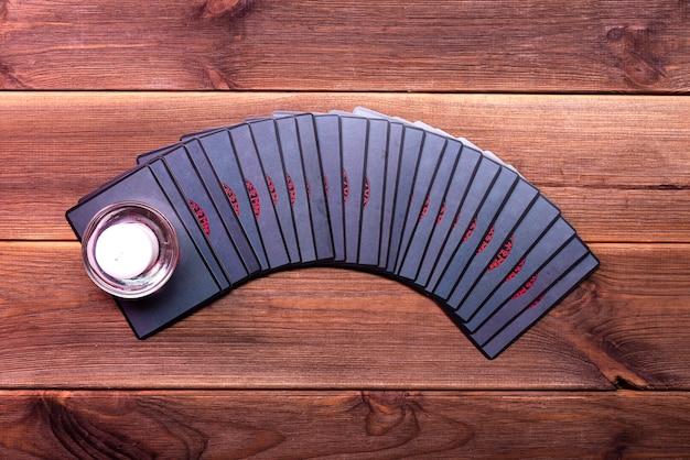 Cartes de fortune sur une table en bois avec une bougie allumée. vue de dessus. cartes runiques.