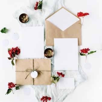 Cartes d'invitation de mariage, enveloppes d'artisanat, roses roses et rouges et feuilles vertes sur blanc