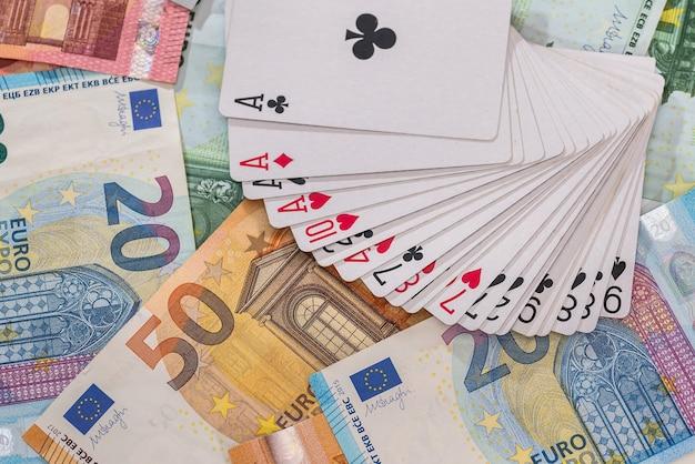Cartes à jouer sur fond de billets en euros, gros plan
