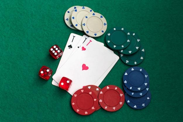 Cartes à jouer, dés et jetons de poker d'en haut sur une table de poker verte