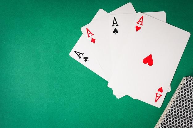 Cartes à jouer, quatre as sur fond vert.