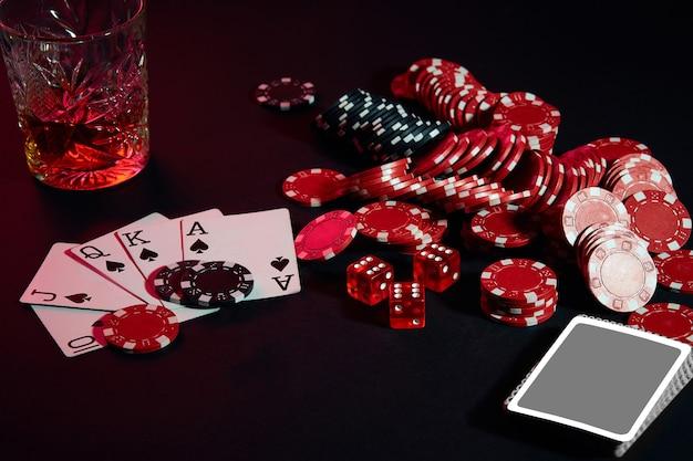 Cartes de joueur de poker. sur la table, des chips et un verre de cocktail au whisky. nature morte. le concept de jeu. poker en ligne. combinaison de cartes - quinte royale