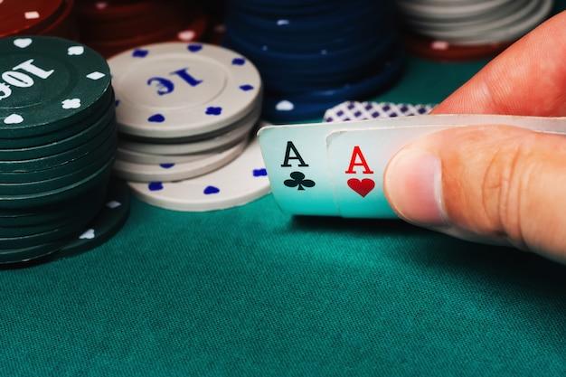 Cartes avec une paire d'as dans le jeu de poker entre les mains d'un joueur sur fond de jetons