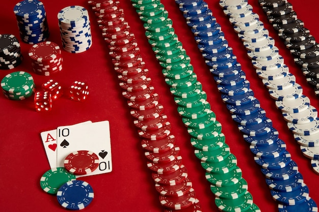 Cartes de poker et jetons de jeu sur fond rouge. vue de dessus. espace de copie. nature morte. mise à plat. cartes - as et dix