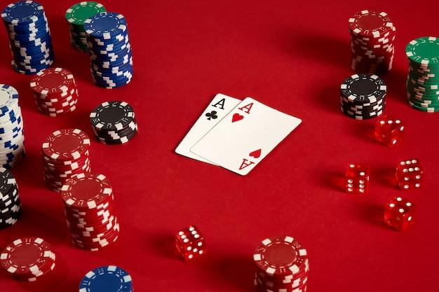 Cartes de poker et jetons de jeu sur fond rouge. vue de dessus. espace de copie. nature morte. mise à plat. cartes - deux as
