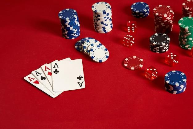 Cartes de poker et jetons de jeu sur fond rouge. vue de dessus. espace de copie. nature morte. mise à plat. cartes - quatre as. 4 d'une sorte