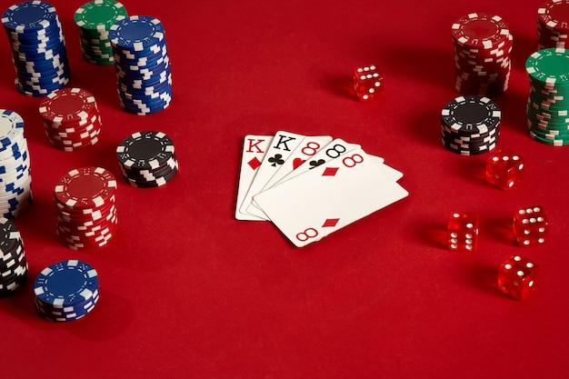 Cartes de poker et jetons de jeu sur fond rouge. vue de dessus. espace de copie. nature morte. mise à plat. full house