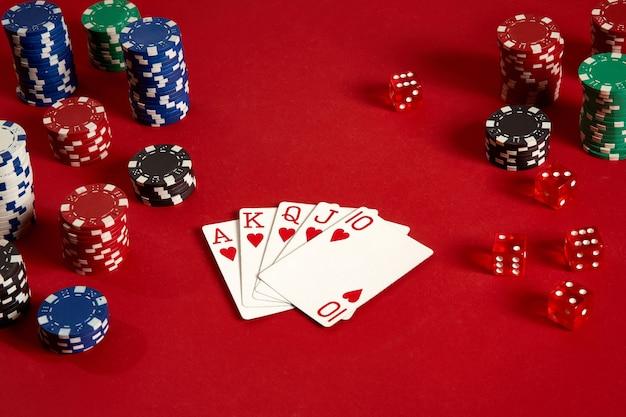 Cartes de poker et jetons de jeu sur fond rouge. vue de dessus. espace de copie. nature morte. mise à plat. quinte royale