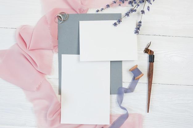 Cartes vierges blanches avec anneaux de mariage et tissu rose avec des fleurs de lavande