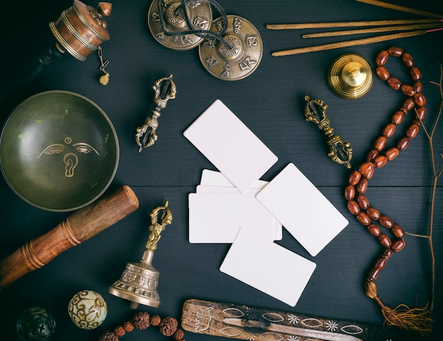 Cartes de visite blanches vides au milieu d'objets religieux asiatiques pour la méditation et la médecine alternative