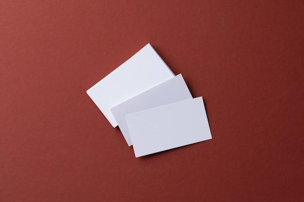 Cartes de visite blanches vierges sur fond de papier bordeaux