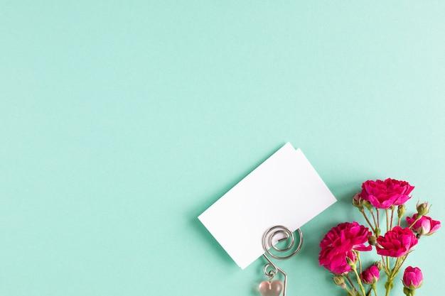 Cartes de visite de maquette sur un fond coloré et une fleur rose, fond, vue de dessus.