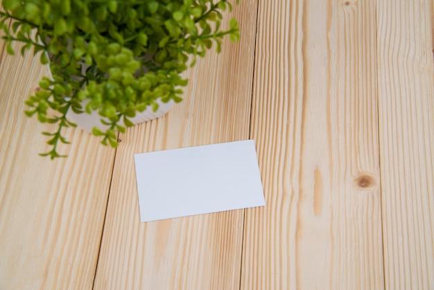 Cartes de visite vierges et petit arbre décoratif sur bois