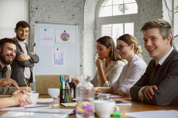 Cartographie du cerveau. groupe de jeunes professionnels ayant une réunion. un groupe diversifié de collègues discute de nouvelles décisions, plans, résultats, stratégie. créativité, lieu de travail, affaires, finance, travail d'équipe.