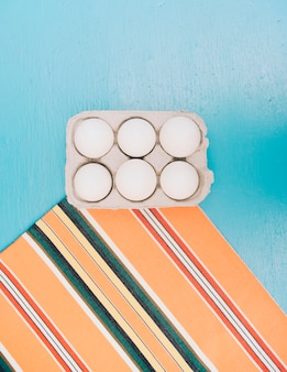 Carton d'oeufs sur tapis contre toile de fond bleue