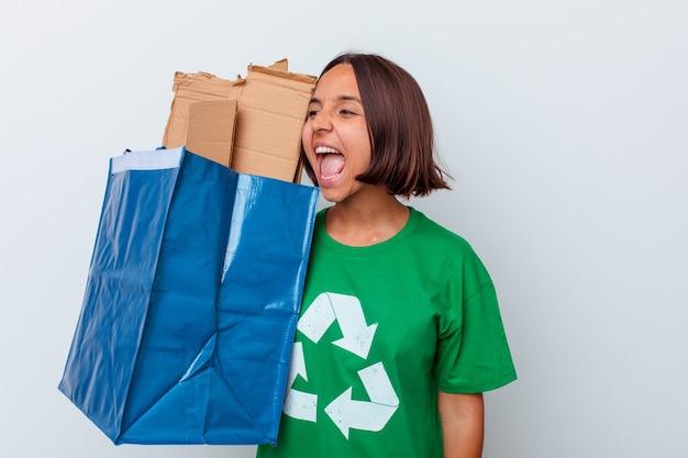 Carton de recyclage femme jeune métisse isolé sur fond blanc criant et tenant la paume près de la bouche ouverte.