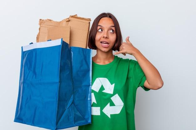 Carton de recyclage femme jeune métisse isolé sur fond blanc montrant un geste d'appel de téléphone mobile avec les doigts.
