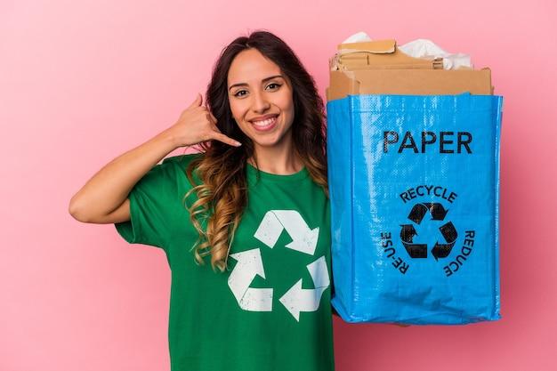 Carton de recyclage de jeune femme mexicaine isolé sur fond rose montrant un geste d'appel de téléphone mobile avec les doigts.