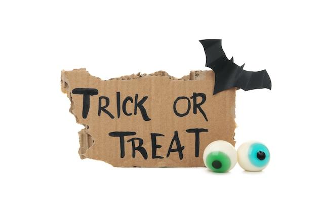Carton avec texte trick or treat, chauve-souris et oeil isolé sur blanc
