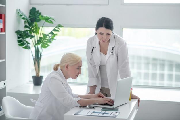 Cas grave. deux femmes médecins regardant l'écran et à la recherche de graves
