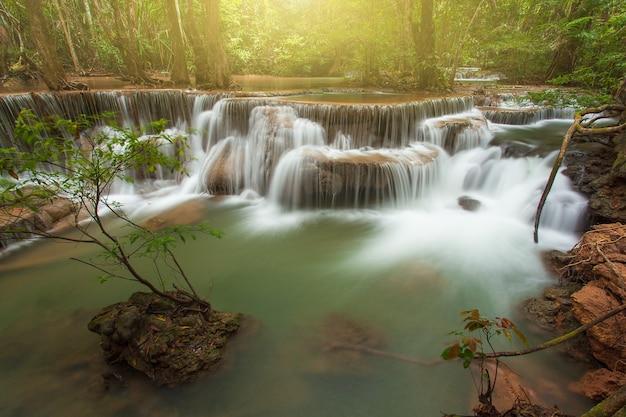 Cascade dans la forêt tropicale à l'ouest de la thaïlande avec la lumière du soleil orange en arrière-plan. prise de vue à vitesse lente. cascade de huai mae khamin, province de kanchanaburi.
