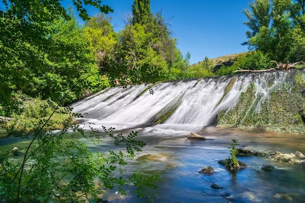 Cascade d'eau glissant sur le mur de pierre dans la forêt de plantes vertes. duraton, sepulveda, ségovie,