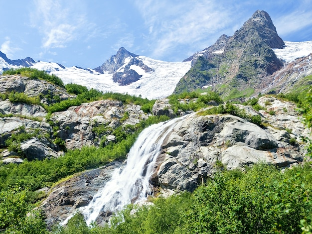 Cascade énorme parmi les montagnes rocheuses couvertes de neige
