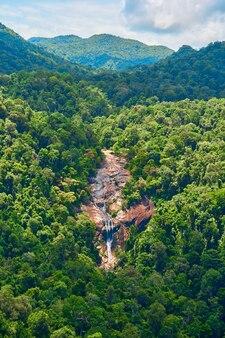 Une cascade majestueuse descend de la falaise dans la jungle dense.