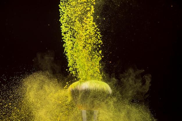 Cascade de poudre de couleur tombant sur un pinceau