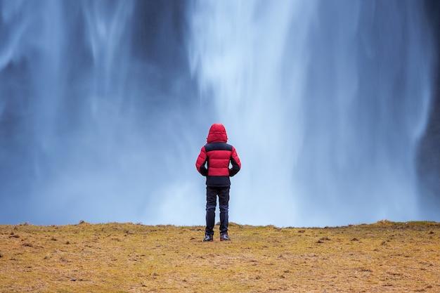 Cascade de seljalandsfoss en islande. guy en veste rouge regarde la cascade de seljalandsfoss.