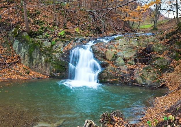 Cascades sur rocky stream, qui traverse la forêt de montagne d'automne