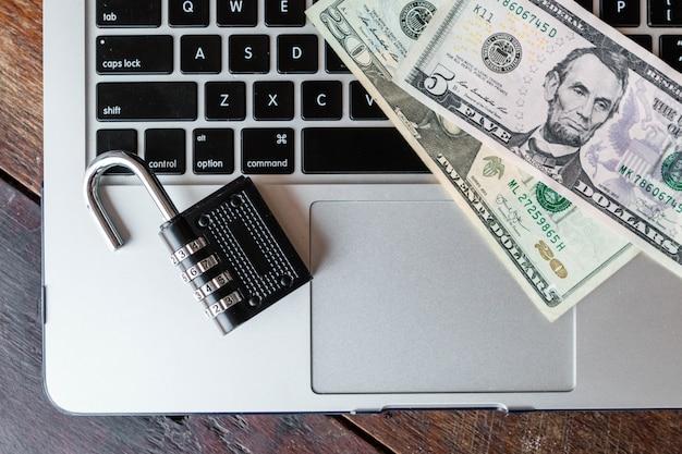 Casier et dollars sur un ordinateur portable. idée de transactions en ligne.