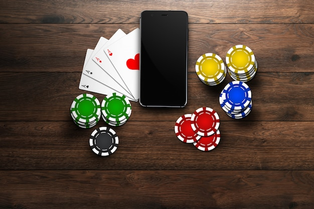 Casino en ligne, casino mobile, vue de dessus d'un téléphone portable, cartes à jetons sur bois