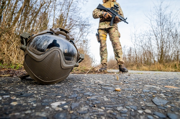 Casque airsoft sur le terrain et une fille en uniforme militaire à l'arrière-plan