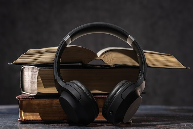 Casque allongé à côté de vieux livres. concept de livre audio.