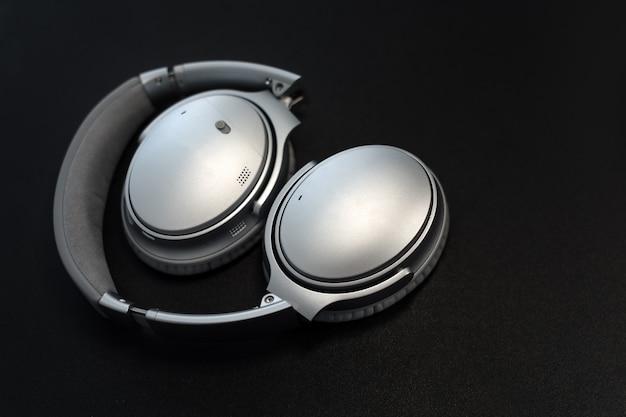 Casque audio de musique. objet d'équipement de volume stéréo. casque sur fond noir et zone de fond pour le texte. technologie audio, gadgets et concept musical.