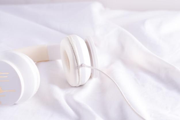 Casque blanc pour la musique sur un lit blanc