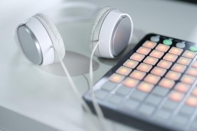 Casque blanc se trouvant près du concept de console de mixage de musique