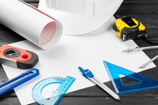 Casque blanc et une variété d'outils de réparation sur fond en bois