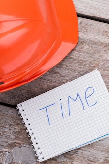 Casque et bloc-notes de l'ouvrier constructeur avec mot de temps. vue de dessus en gros plan.